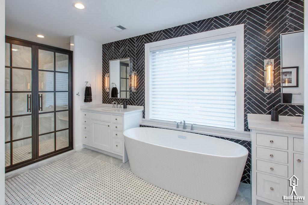 Round bathtub with black herringbone tile