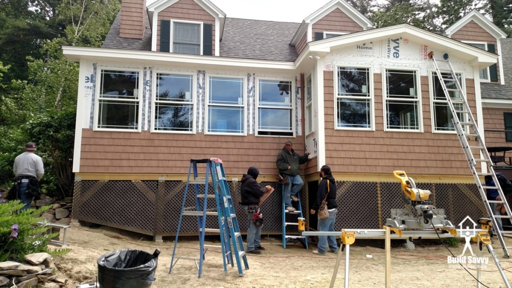 Construction workers working on putting siding on a house