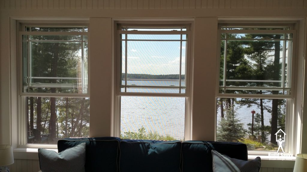 A view of the three porch windows overlooking a lake